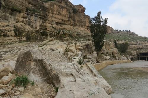 De uitgehouwen stier op de voorgrond, en daarachter de rotsen met resten van andere Assyrische sculpturen