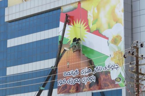 Vandaag is het een feestdag, maar 's ochtends moet nog de laatste hand worden gelegd aan de patriottische versieringen: een enorme poster met de Koerdische vlag en narcissen als symbool voor de lente.